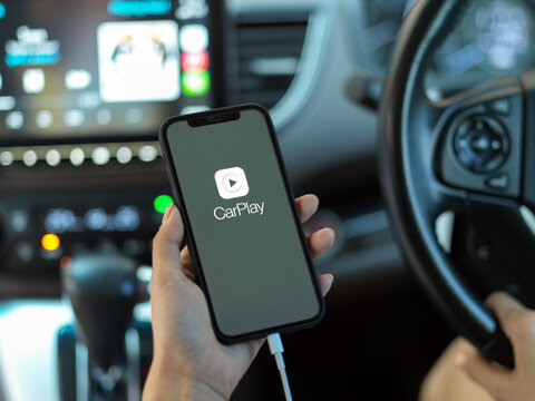 CHIANG MAI, THAILAND - MAY 11, 2020 : hand holding smartphone with CarPlay application. CarPlay is a application allows you to view content from your iPhone on your car's infotainment screen