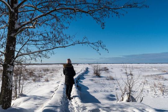 Woman on a footpath in a frozen wetland