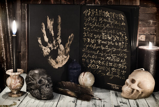 Evil book wih black pages and mystic symbols, burning candles and skull on wooden table. Sell soul to the devil concept.
