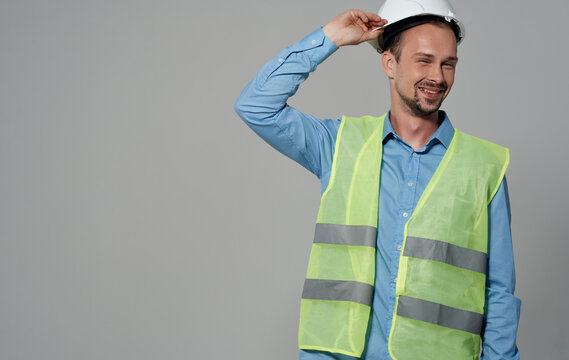 A man in a yellow vest with a helmet on his head construction engineer repair work