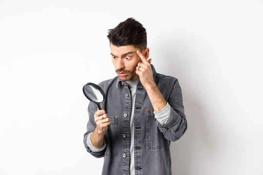 Man looking through magnifying glass and stretching eyelid to see clearly, standing on white background