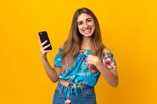 Young woman using mobile phone over isolated yellow background with surprise facial expression