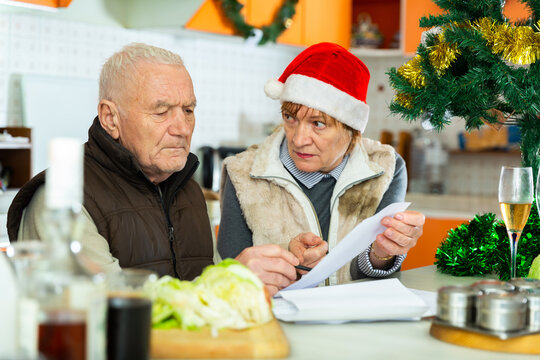 Image of aged family trying to pay utility bills before new year dinner