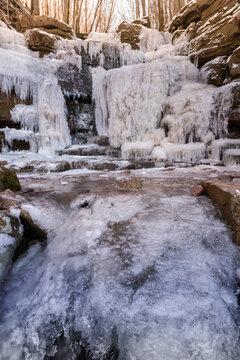 Waldschlucht mit Wasserfall im Winter, gefrorenes Eis bedeckt Sandsteinfelsen.