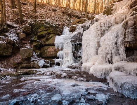 Naturschauspiel in einer Waldschlucht, gefrorener Wasserfall im Winter, Eisstarre im Dauerfrost.
