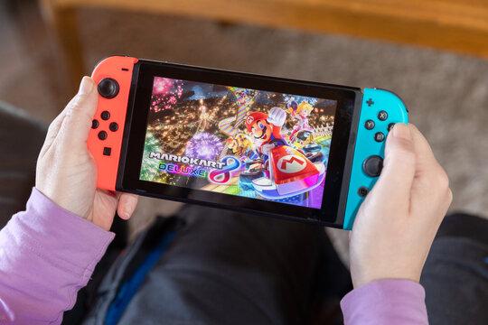 IBBENBUEREN, GERMANY - FEBRUARY 14, 2021: mario kart deluxe 8 popular Nintendo switch with joy controllers family friend activity
