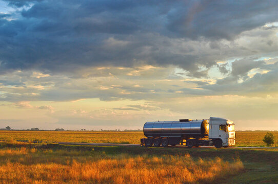 Truck driving on a road at sunset. Beautiful early evening cloudy sky. Sunlit grass in the foreground