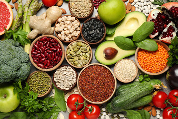 Different vegetables, seeds and fruits on grey table, flat lay. Healthy diet
