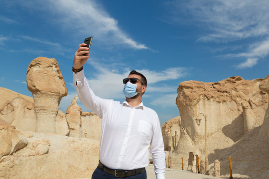 Lonely male tourist at Al Qarah Mountain taking selfie with mask