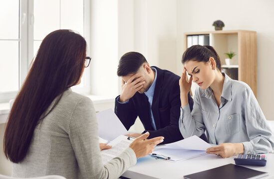 Financial problems. Couple getting very bad news from real estate agent, bank manager or lawyer. Sad clients reading bankruptcy notice or mortgage contract with disadvantageous terms and conditions