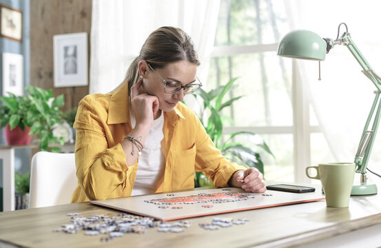 Woman sitting at desk and solving a puzzle