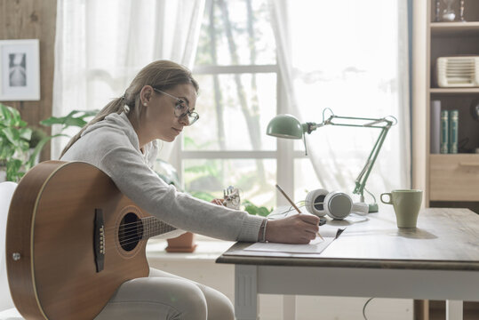 Woman playing guitar and composing music
