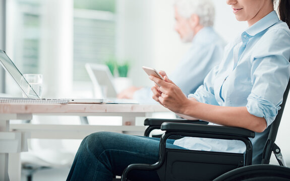 Businesswoman in wheelchair using a smart phone