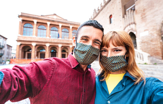 Happy girlfriend and boyfriend in love taking selfie covered by face mask at old town tour - New normal life style travel concept with tourist couple on city sightseeing vacation - Warm vivid filter