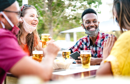 Multicultural people drinking beer with open face masks - New normal gathering concept with friends having fun together on happy hour at brewery bar - Bright filter with focus on afroamerican guy
