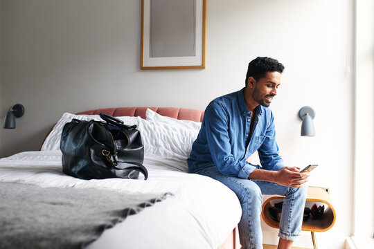 Man Staying In Boutique Hotel Sits On Edge Of Bed Checking Emails And Social Media In The Morning