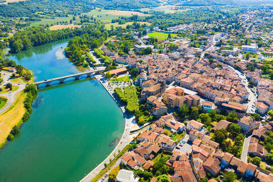 View from drone of cityscape of small French town of Cazeres on river Garonne in summer