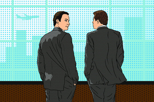 Two young business men in suits stand in the office near the window, look at the city and have a conversation.