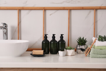 Soap dispensers, towels and plants on countertop in bathroom