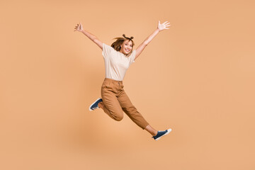 Wall Mural - Full length photo of girl jump having fun wear t-shirt pants sneakers isolated beige color background