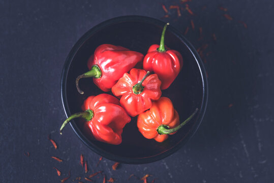 Scotch Bonnet pepper or Caribbean red hot peppers  on the dark rustic background, macro