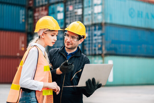 workers teamwork man and woman in safety jumpsuit workwear with yellow hardhat and use laptop check container at cargo shipping warehouse. transportation import,export logistic industrial service