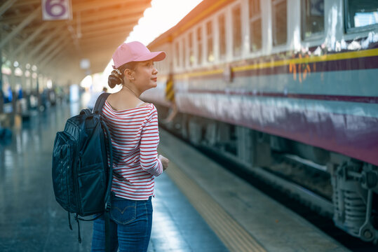 Young woman traveler waiting for a train on a train on platform of railway station, travel and active lifestyle concept