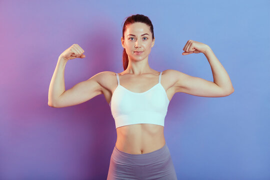 Young strong woman looking directly at camera, raising both hands and showing her biceps, wearing top and leggins, isolated over color background, lady with perfect body and ponytail.