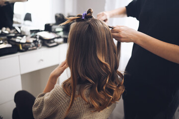 Hair stylist prepares beautiful young woman for event, makes curls hairstyle with a curling iron for client in beauty salon. Long beautiful light brown natural hair.