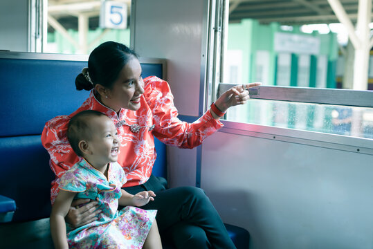 Asian mother and her infant daughter enjoy travelling by train. Mother points finger outside the window, daughter happy and laughing.