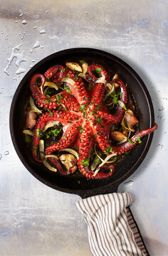 Octopus Lagareiro style dressed with onion and garlics cloves on an aged metallic table. Portuguese cuisine.