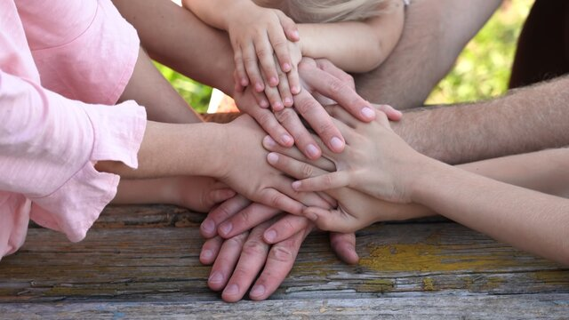 A friendly family joins their hands as a sign of joint success.