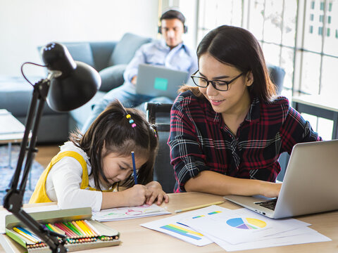 Muti ethnic family, father, and mother and young little daughter stay together in living room. Mom work from home with laptop notebook computer while teaching girl to do homework. New normal concept