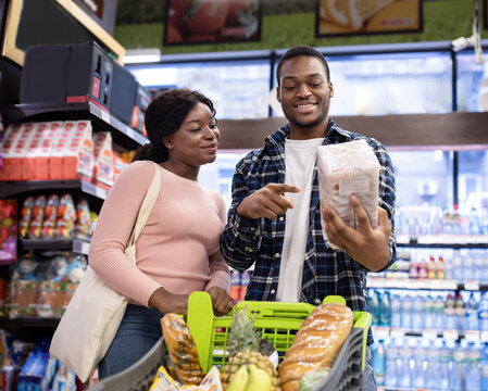 Attractive black woman and her husband shopping for groceries at supermarket, choosing products of best quality