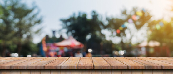 Empty wood table and defocused bokeh and blur background of garden trees in sunlight, display...