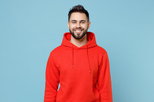 Young caucasian smiling happy cheerful bearded attractive handsome student man 20s wearing casual red orange hoodie looking camera isolated on blue background studio portrait People lifestyle concept.
