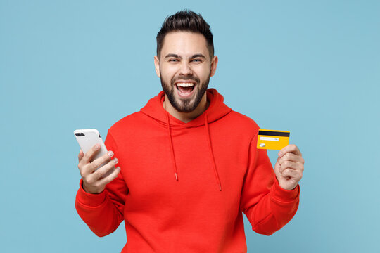 Young caucasian smiling overjoyed excited bearded man 20s wearing casual red orange hoodie hold mobile cell phone credit bank card isolated on blue background studio portrait Online shopping concept.