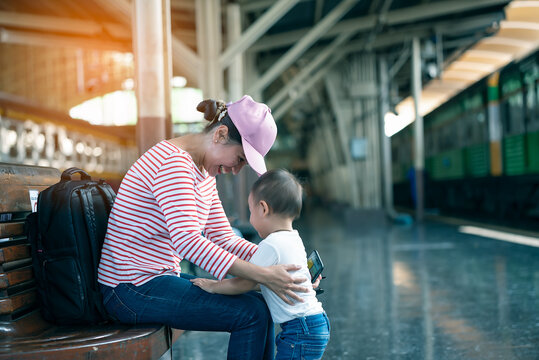 Young Aian mother playing with her little infant kids while waiting for the train on train platform. Both are happy and laughing together.