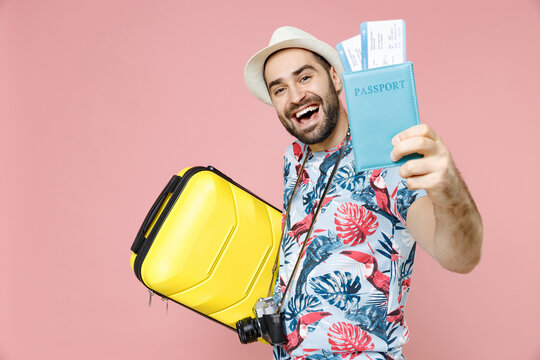 Laughing young traveler tourist man in summer clothes hat photo camera hold suitcase passport ticket isolated on pink background studio. Passenger traveling on weekend. Air flight journey concept.