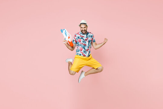 Full length of happy traveler tourist man in summer clothes hat jumping hold toy water gun doing winner gesture isolated on pink background. Passenger traveling on weekend. Air flight journey concept.