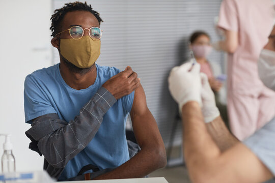 Portrait of modern African American man taking covid vaccine at vaccination center, copy space