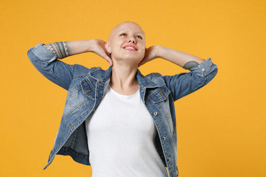 Young bald smiling caucasian positive woman 20s without hair wearing casual denim jacket white t-shirt relax enjoy stretching holding hands behind head isolated on yellow background studio portrait.