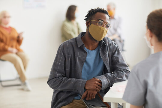 Portrait of young African American man wearing mask while talking to doctor or nurse in ,medical clinic, copy space