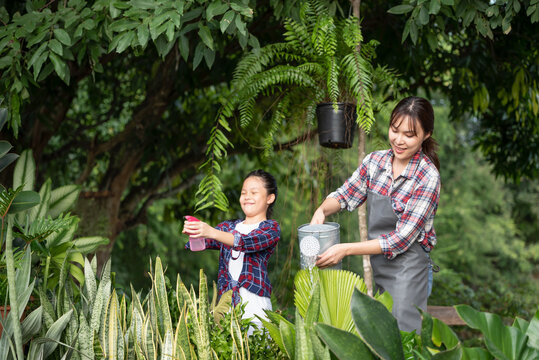 Young Asian mother and daughter happy working in the gardern together on weekend. Daughter helping mother watering.