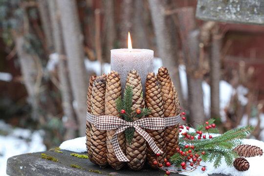 rustikale Winter-Gartendekoration mit Kerze und Tannenzapfen
