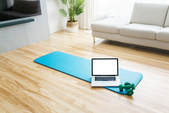 Online workout at home gym concept. Laptop computer on yoga mat on floor in living room in modern apartment interior