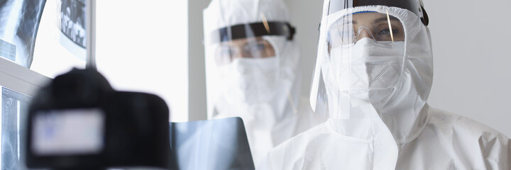 Doctors in protective screens and anti-plague suits looking into camera in X-ray room. Blogging...