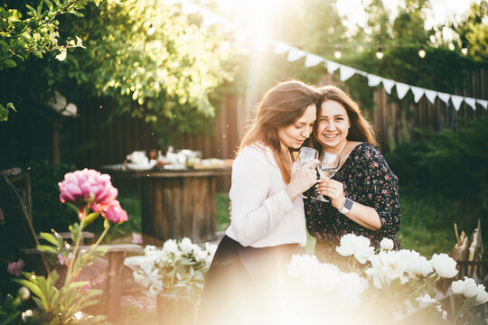 Mother and Daughter Embracing at backyard party.