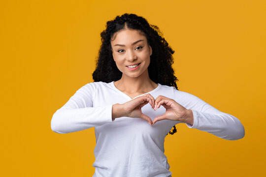 Beautiful young black lady making heart gesture with hands near chest