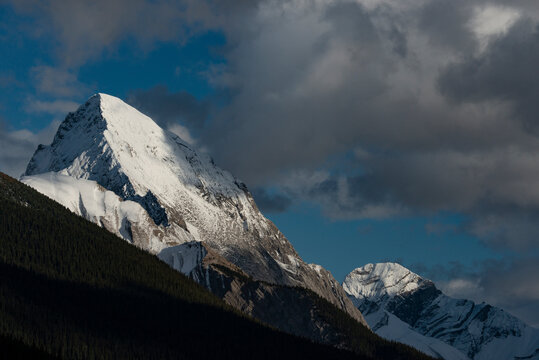 Canada, Alberta. Leah and Samson Peaks, with snow and clouds, Maligne Lake, Jasper National Park.